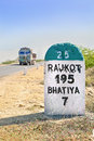 Vertical take of kilometer milestone and direction sign to rajkot in gujarat india with a typical truck about to pass by rural Stock Photography