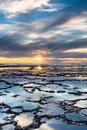 Vertical View Of A Beautiful Sunset Over The Ocean With Rocky Beach And Tidal Pools In The Foreground