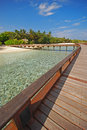Vertical view of spacious wooden walkway on an island paradise connecting guest to exclusive overwater villa Royalty Free Stock Photography