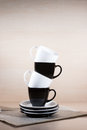 Vertical view of standing black and white cups on the stack of the plates on newspaper. Royalty Free Stock Photo
