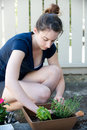 Vertical of woman planting plants in the shade Royalty Free Stock Images