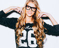 Very beautiful girl with long blond hair pointing finger at her fashionable glasses. Close up. Indoor. Warm color. Royalty Free Stock Photo