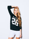 Very beautiful girl with long blond hair posing on a white background. She raised her hand above her head and smiling. Sweatshirt Royalty Free Stock Photo