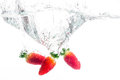 Very berry three strawberries being cast into fresh water Stock Image