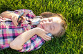 Very cheerful and funny little girl listening to music in the green grass Stock Image