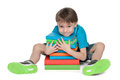 Very clever little boy with books is sitting on the floor near the pile of on the white background Stock Image