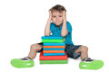 Very clever thoughtful little boy is sitting on the floor near the pile of books on the white background Royalty Free Stock Image