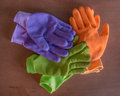 Very colorful work gloves three pairs of on a wood surface orange purple and green Stock Photo