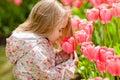 Very cute beautiful girl blonde in pink coat costs around flower