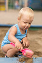 Very diligent builder from sand cute little baby boy playing in the sandbox on the playground Royalty Free Stock Images