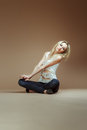 Very expressive blonde girl in a white torn top and jeans sit on the floor Stock Photos