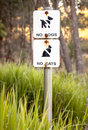 Very faded sign in nature reserve no dogs no cats weathered and australian environmental conservation area stating to preserve Stock Photo