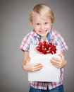 Very happy boy holding present a cute young a large gift or and smiles at camera Stock Image