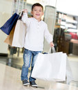 Very happy boy holding shopping bags mall Royalty Free Stock Image