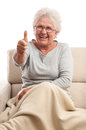 Very happy old woman thumb up sitting on the sofa and gesturing thumbs big laugh blanket on feet isolated on white background Royalty Free Stock Photos