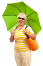 Very happy senior woman with sun umbrella old in vivid colored clothes going on the beach laughing having fun summer time isolated Stock Photo