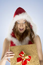 Very happy xmas woman opening gift box portrait of pretty girl with christmas style red fur hood and surprised expression with red Royalty Free Stock Image