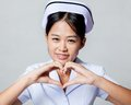 Very happy young Asian nurse show heart hand sign Royalty Free Stock Photo
