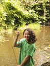 Very happy young girl catches small trout vertical photo of smiling while holding up with stream and trees in background Royalty Free Stock Photo