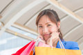 Very happy young woman with shopping bags, at centre or mall. Royalty Free Stock Photo