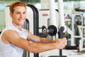 It is very important to stay fit handsome young man working out in gym and smiling Stock Photo