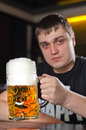A very large litre tankard of beer young man in pub holding up with good frothy head with focus to the glass Stock Photo