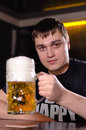 A very large litre tankard of beer young man in pub holding up with good frothy head with focus to the glass Stock Photography