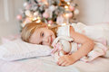 Very nice charming little girl blonde in white dress lying on th