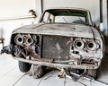 Very old and decrepit car awaiting restoration rusty once green propped up on wood junk waiting for Royalty Free Stock Photos