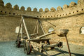 Very old gun for throwing stones to be protected. Old castle walls Royalty Free Stock Photo