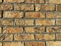 A very old retro style cracking and crumbling orange and red brick wall in a warehouse building alley showing bright detailed Royalty Free Stock Photo