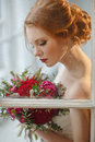 Very pretty sophisticated red-haired girl with a bouquet in his Royalty Free Stock Photo
