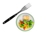 Very small plate of food with large fork a diet meal haddock and vegetables an oversized to the side Stock Image