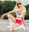 A very stunner smiling closeup portrait of sexy young woman posing in a vintage roller skates, sunglasses, T-shirt, shorts posing Royalty Free Stock Photo