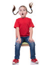 very surprised little girl with funny pigtails wearing red t-short and sitting on the chair Royalty Free Stock Photo