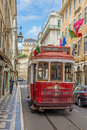 Very touristic place in the old part of Lisbon, with a traditional tram passing by in the city of Lisbon, Portugal.