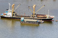 Vessel bulk cargo beside cargo boat with crane and lighter in the river Stock Photos
