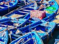 Vibrant blue wooden boats lined up in the harbor Royalty Free Stock Photo