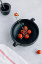 Vibrant Cherry Tomatoes on the Vine in Dark Clay Rustic Pot on Grey Kitchen Worktop Royalty Free Stock Photo