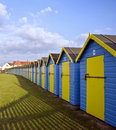 Vibrant colorful beach huts along beach Stock Photos