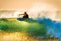 Vibrant light surfer on performance short board floating off the closing lip of a back lit wave at dawn during large surf Royalty Free Stock Images