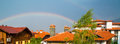Vibrant Rainbow behind the roofs and trees Royalty Free Stock Photo