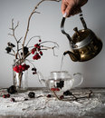 Viburnum branches with berries and snow in a transparent vase, female hand pouring water into the kettle.