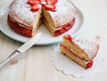 Victoria sponge cake with strawberries with a cut piece on a wooden table jam and whipped cream out horizontal Stock Photos