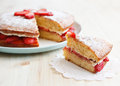 Victoria sponge cake with strawberries with a cut piece on a wooden table jam and whipped cream out horizontal Stock Photography