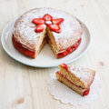 Victoria sponge cake with strawberries with a cut piece on a wooden table jam and whipped cream out square Royalty Free Stock Photography