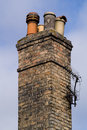 Victorian domestic chimney with four assorted chimney pots against a clear blue sky background close up vertical Royalty Free Stock Images