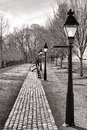 Victorian street reproduction with streetlights antique american style vintage gaslight inspired and old cobblestone sidewalk as Royalty Free Stock Image