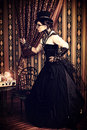 Victorian time full length portrait of a beautiful steampunk woman over vintage background Stock Image