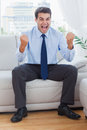 Victorious businessman cheering while sitting on sofa in cosy bright office Stock Image